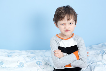frowned: Naughty little boy. Angry little boy frowned while sitting in bed in pajama and looking at camera Stock Photo