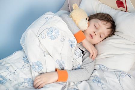 자신의 침대에서 잠을 어린 소년. 곰 포옹