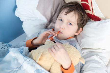 Little boy lying sick in bed. In the mouth, holding a thermometer to measure body temperature. hugs a teddy bear photo