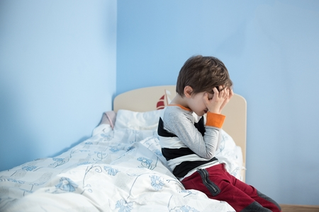 fear child: Sad, upset little boy sitting on the edge of his bed. Covering his face with hands. Stock Photo