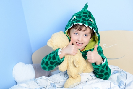 thumbs: Portrait of little boy gesturing thumbs up with teddy bear in bed.  A child dressed in a funny bathrobe