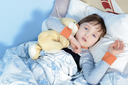enfant malade: Portrait d'un gar�on malade serrant un ours en peluche couch� dans un lit Banque d'images