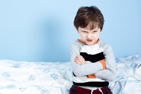 maltrato infantil: Niño travieso. Niño pequeño enojado frunció el ceño mientras se está sentado en la cama en pijama y mirando a cámara Foto de archivo