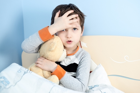 Sick little boy hugs his teddy bear in bed. Touching his forehead to check temperature