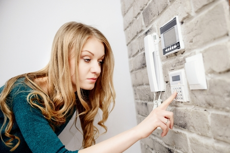 introduces: Beautiful young blond woman activates an alarm in the house. Introduces a code using the keypad Stock Photo