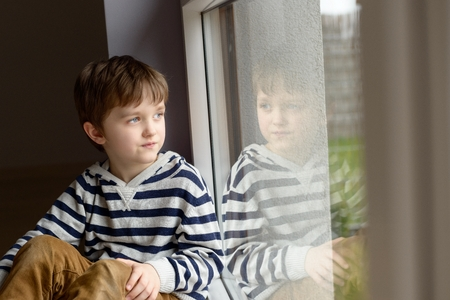 Thoughtful little boy sitting by the window looking out onto the garden Stock Photo
