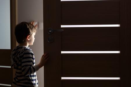 Little boy opens the door to the room by night Foto de archivo