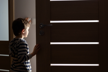 Little boy opens the door to the room by night Stockfoto