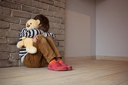violencia: Niño pequeño triste que se sienta contra la pared en la desesperación. En sus manos sostiene un viejo amigo el oso de peluche