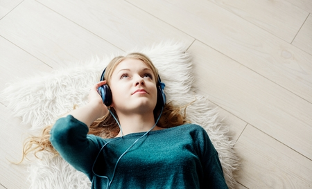Beautiful blond woman listening to music through headphones. Lying on a wooden floor. 写真素材