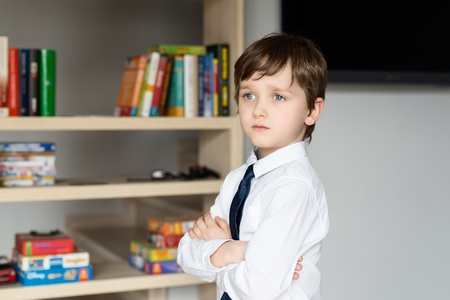 boy room: Elegantly dressed in a white shirt and tie little boy stands in front of a shelf of books. Crossed arms