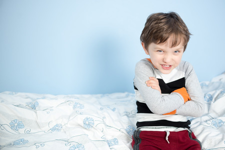 6 year old: Cute 6 year old boy sitting on the edge of the bed happy with crossed arms