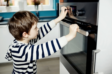 dangerous: Curious little boy dangerously playing with the knobs on the oven. Danger at home