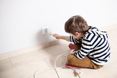 peligro: Niño curioso que juega con enchufe eléctrico. Tratando de insertarlo en la toma de corriente. Peligro en casa
