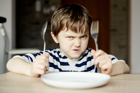 Furious little boy waiting for dinner. Holding a spoon and fork in the hand Stock Photo