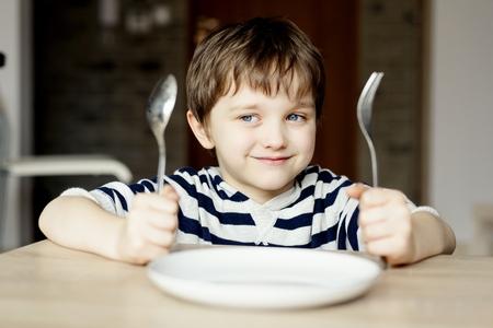 夕食を待っている幸せ小さな男の子。スプーンとフォークを手に持ってください。