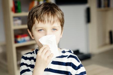 bebe enfermo: El niño pequeño sopla su nariz en un pañuelo de papel Foto de archivo