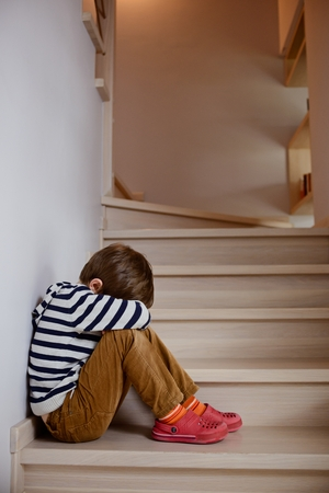 Sad little boy crying depressed sitting on the stairs