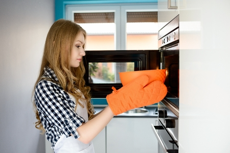 Young blond woman pulls out a hot bowl of  microwave. Protective orange gloves on her hands.
