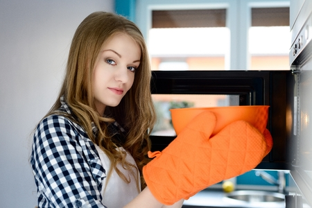 preparing food: Young blond woman pulls out a hot bowl of  microwave. Protective orange gloves on her hands. Looking at camera
