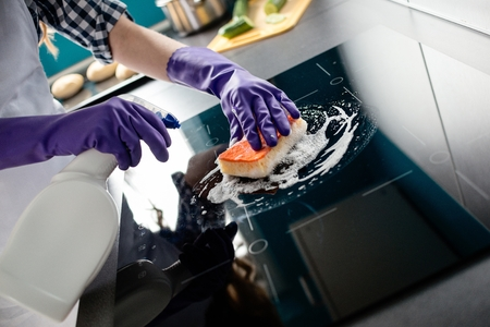 work from home: Womans hands cleaning kitchen top in purple rubber protective gloves