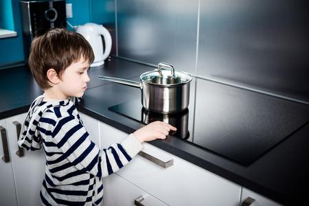 Lindo niño de 6 años aumenta la potencia de calefacción bajo la olla en la estufa de inducción Foto de archivo