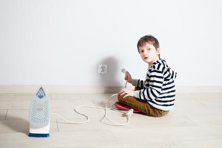 peligro: Pequeño bebé que juega peligrosamente con el alambre eléctrico de hierro. Tratar de introducir el enchufe en el contacto