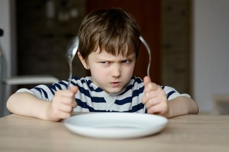 niños sentados: Niño pequeño trastornado espera para la cena mientras sostiene un tenedor y una cuchara Foto de archivo