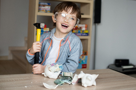 young pig: Little boy broke his piggy bank. Smiling, safety glasses on his eyes