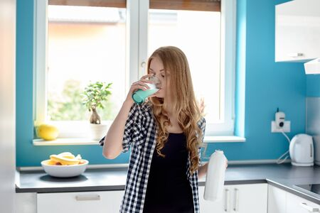 woman drinking milk: Thirsty young blond woman drinking milk from a glass in the kitchen. Holding the bottle in the other hand