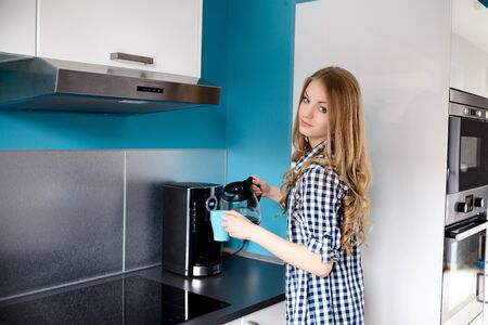 kitchen device: Young blond woman pours coffee from a coffee maker to cup  in the kitchen Stock Photo