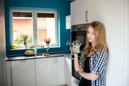 woman drinking milk: Young blond woman drinking milk from a glass in the kitchen.