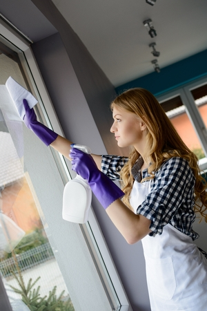 up service: Portrait of attractive young woman cleaning windows in the house