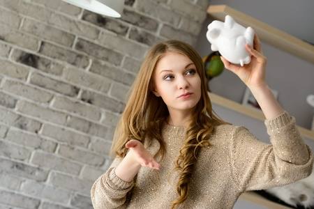 Young blond woman trying to find more money in the piggy bank, lifting it over his head