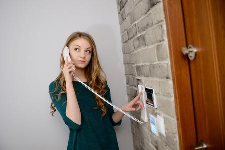 Een mooie jonge blonde vrouw praten over de intercom in het appartement