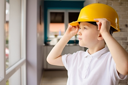 6 year old: 6 year old boy posing by a window with a yellow helmet on his head. Adjusting helmet on his head