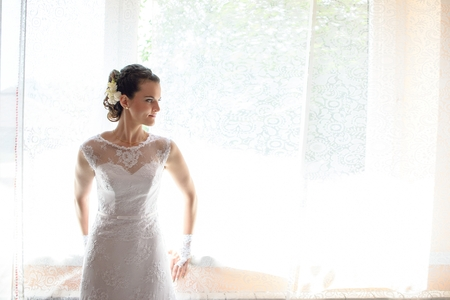 nude bride: Beautiful bride in white wedding dress standing in her bedroom and looking through the window