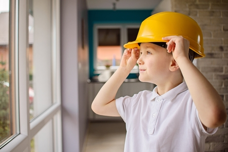 6 year old: Little 6 year old boy posing by a window with a yellow helmet on his head. Adjusting helmet on his head Stock Photo