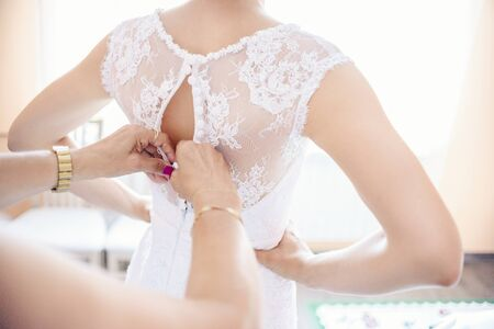 wedlock: Mother helping the bride - her daughter to put her wedding dress on, close up photo Stock Photo