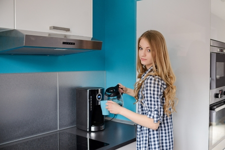 tomando refresco: A beautiful blond woman pours coffee from coffee maker into a cup. Standing in the kitchen. Dressed in a plaid shirt.
