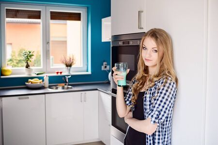 woman drinking milk: Blond woman drinking milk from the glass. Standing in the kitchen. Dressed in a plaid shirt and shorts Stock Photo