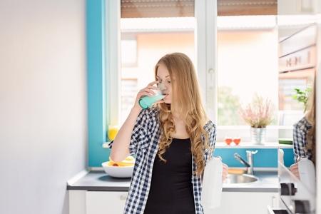 ni�as sonriendo: Mujer rubia joven que bebe la leche de vidrio. De pie en la cocina. Vestido con una camisa a cuadros Foto de archivo