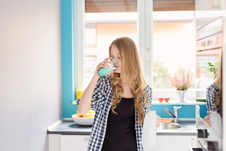 girl glasses: Young blond woman drinking milk from the glass. Standing in the kitchen. Dressed in a plaid shirt