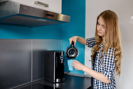 tomando refresco: Mujer rubia joven que vierte el café de la máquina de café en una taza. De pie en la cocina. Vestido con una camisa a cuadros. Foto de archivo