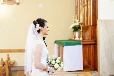 catholic wedding: The bride stands before the altar in the church and holding a bouquet of white flowers