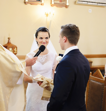 fidelidad: La novia y el novio durante la ceremonia de la boda en la iglesia. La novia promete amor, la fidelidad a su futuro marido