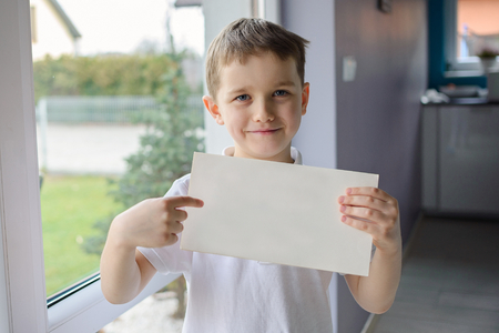 grampa: Happy boy in a polo shirt, holding an empty copyspace sheet of paper. Dressed in a white polo shirt Stock Photo
