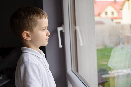 6 year old: Thoughtful 6 year old boy looking out the window into the backyard. Dressed in a white polo shirt