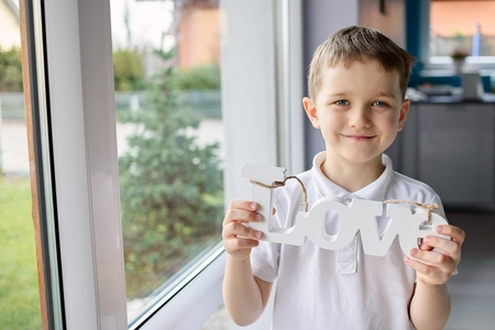 grampa: Happy little boy holding a wooden inscription with the word love. Dressed in a white polo shirt Stock Photo