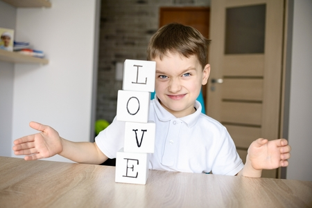 destroying: Frustrated boy destroying brick tower he built. Word love on cubes